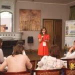 «Обучение в Чехии. Level 2.0», девушка в оранжевом платье в микрофон рассказывет лекцию, eurostudy.cz